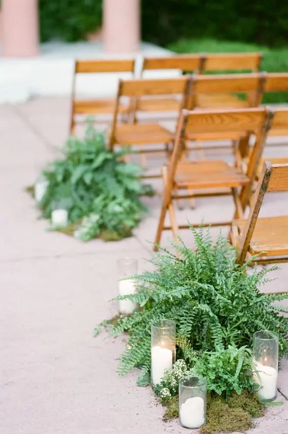 a wedding aisle with moss, ferns and candles for a natural touch, these plants won't wilter