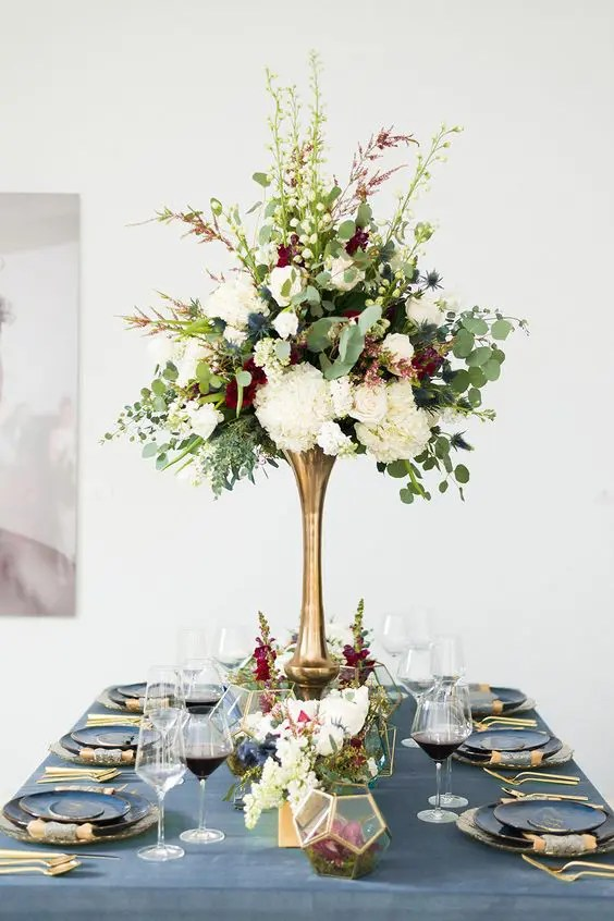 an elegant wedding centerpiece of white, burgundy blooms, thistles and eucalyptus in a brass tall vase
