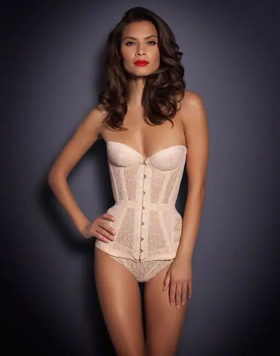 a vintage-inspired blush corset with an accented waist and panties, all lace by Agent Provocateur