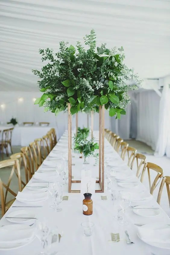 a gorgeous tall wedding centerpiece of lush and textural greenery on a copper stand
