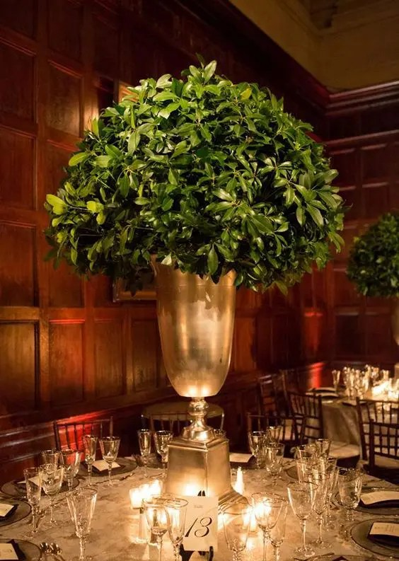 a tall leafy centerpiece in a large gold vase is all you need for modern rustic elegant at the table