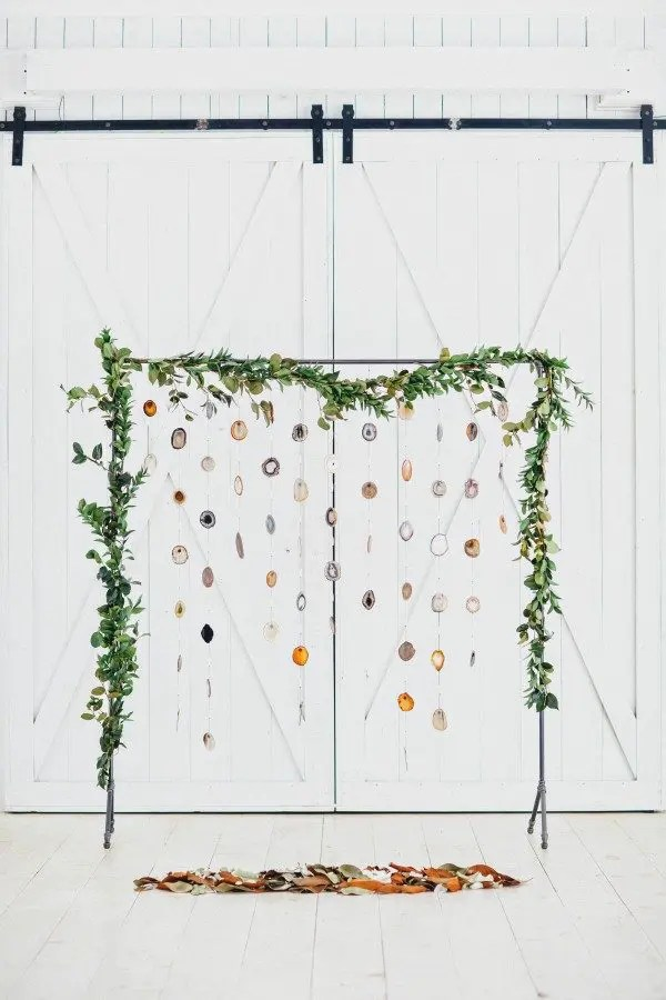 a creative greenery arch with agate slices hanging gown and some leaves under the arch for a boho ceremony