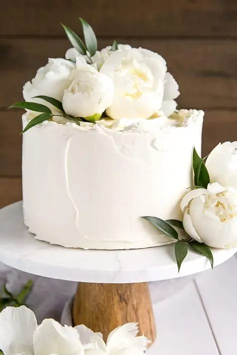 a small textural white wedding cake topped with white peonies for a chic look, texture brings it all