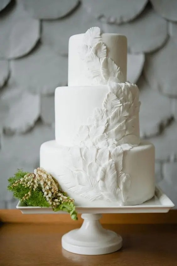 a plain white wedding cake decorated with sugar feathers is a unique idea for a boho chic wedding