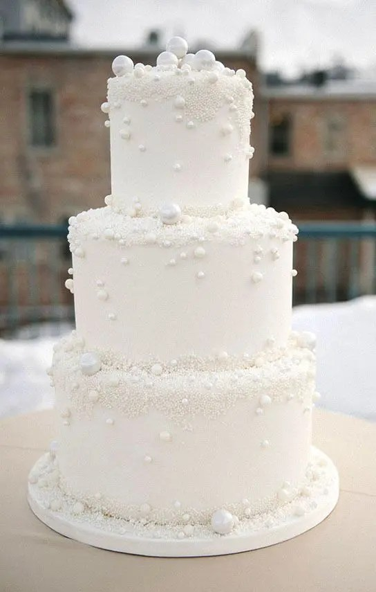 a white wedding cake with sugar pearls attached is ideal for a winter wonderland wedding