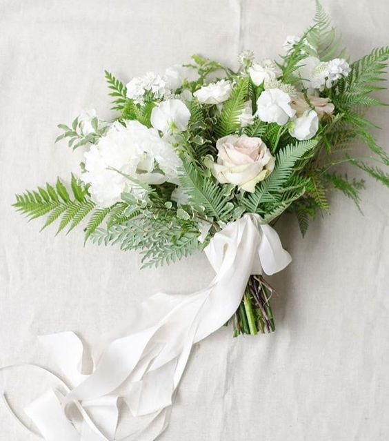 a chic textural white winter wedding bouquet with ferns and white ribbons