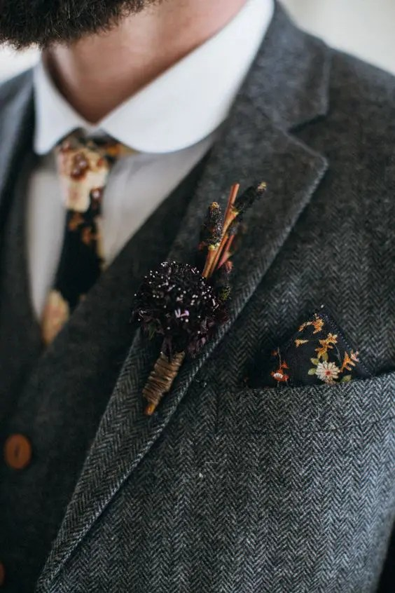 a grey tweed three-piece wedding suit with a moody floral tie and handkerchief plus a herb boutonniere
