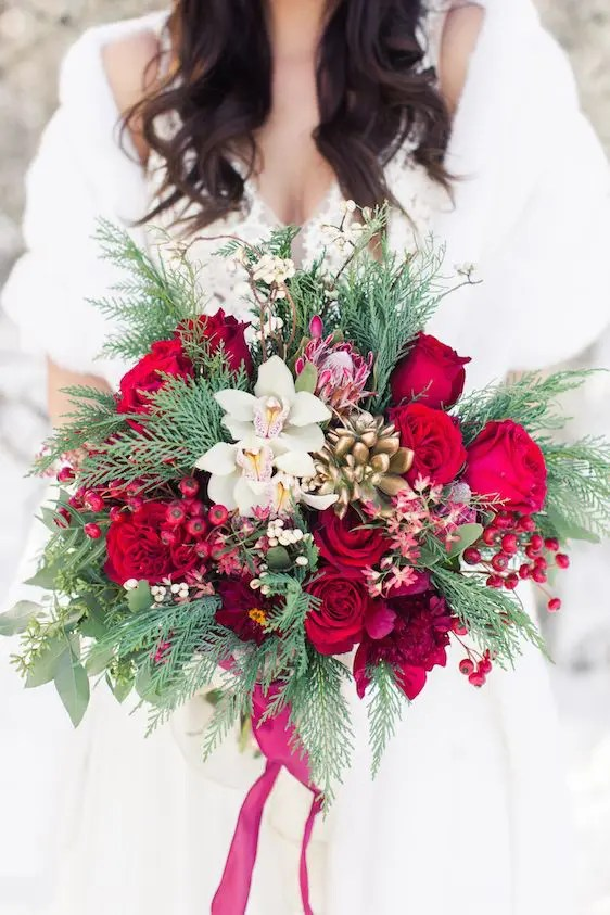 a lush Crhsitmas wedding bouquet with holly berries, bold blooms, orchids, succulents and evergreens