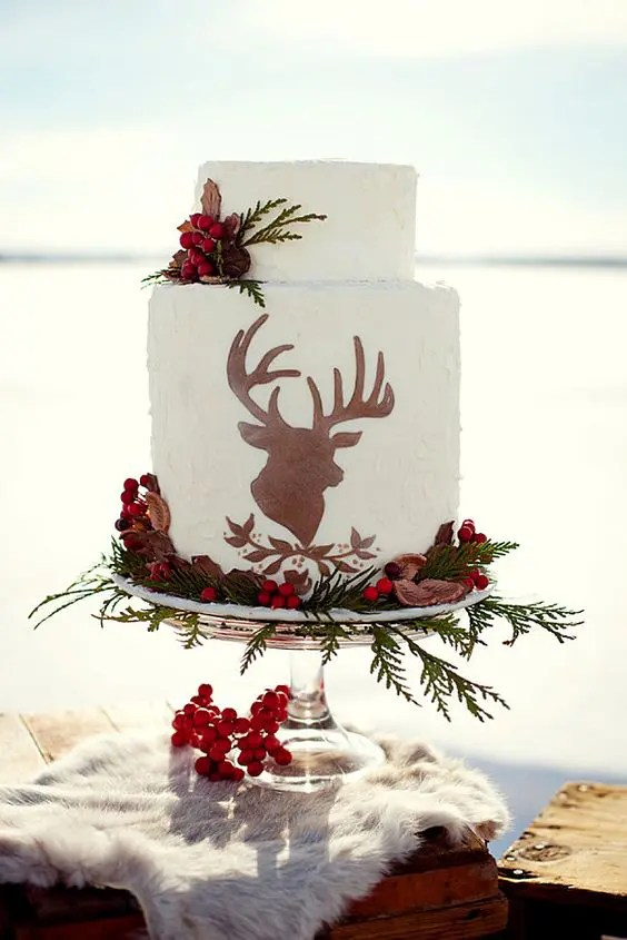 a Christmassy wedding cake with a deer silhouette, greenery, berries and nuts for a woodland wedding