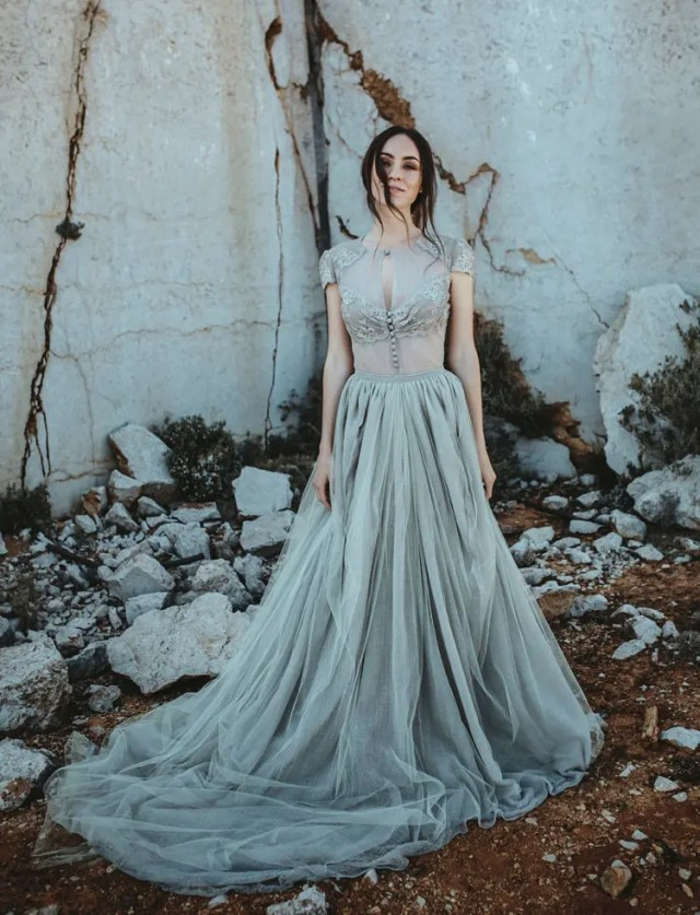 a two piece grey wedding dress with a tulle blouse and a layered full skirt with a train