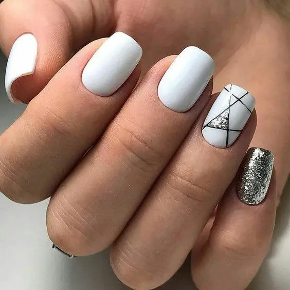 white nails with a single silver glitter one and a geometric one with a touch of silver glitter for a chic holiday look