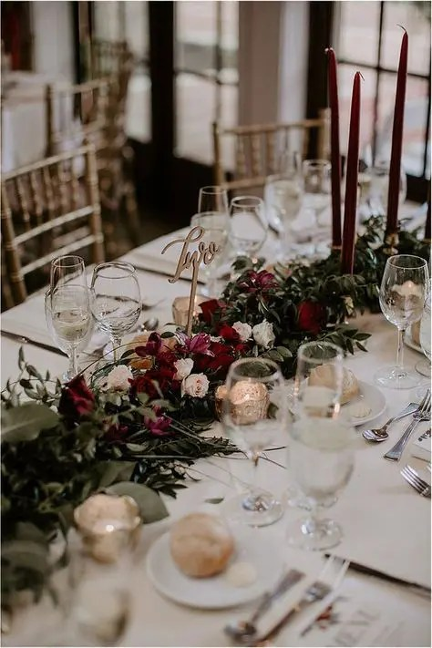a chic floral table runner with lush greenery, blush and burgundy blooms plus matching candles
