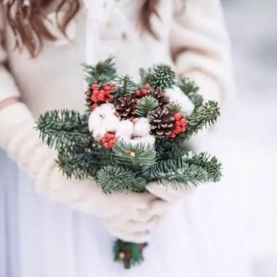 a simple rustic wedding bouquet with evergreens, cotton, pinecones and holly berries