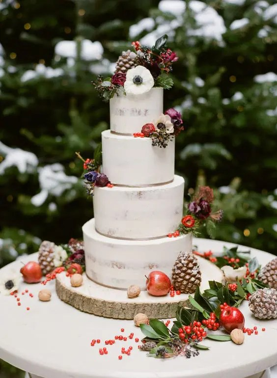 a semi naked wedding cake topped with dark blooms, berries, apples and gilded pinecones