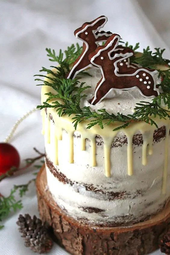 a semi naked wedding cake with white chocolate dripping, greenery and glazed gingerbread cookies on top
