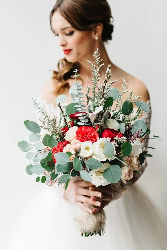 a Christmas wedding bouquet of eucalyptus, white, blush and red flowers plus herbs