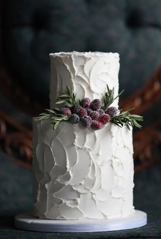 a white textural buttercream wedding cake with evergreens and sugared berries for a clean yet catchy look
