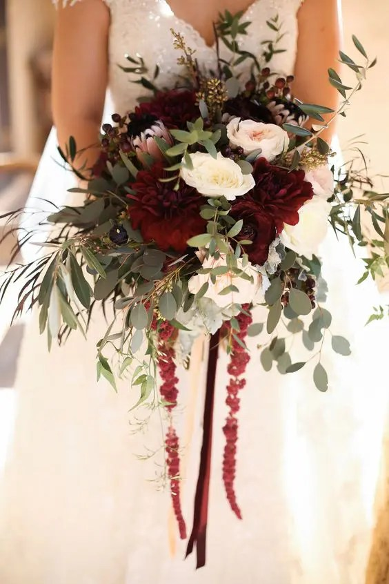 a bright and textural winter wedding bouquet with burgundy, blush and white flowers and lots of greenery