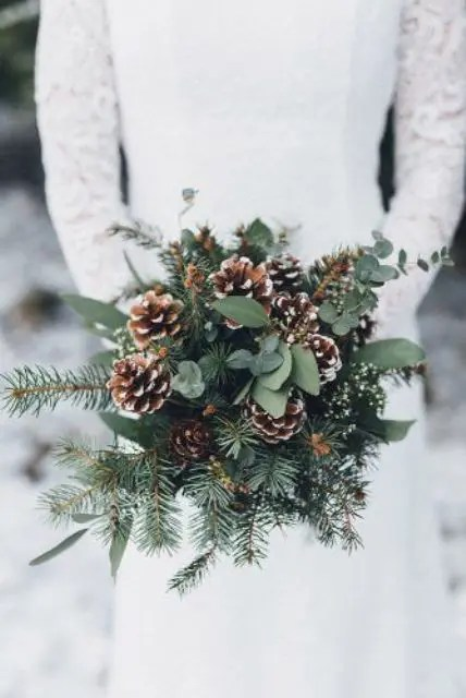 a cozy rustic winter wedding bouquet with evergreens, eucalyptus and snowy pinecones