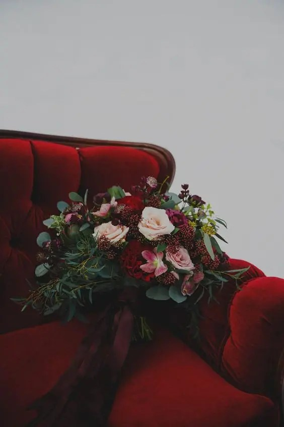 a luxurious rich wedding bouquet of blush and deep red blooms, lots of greenery and berries