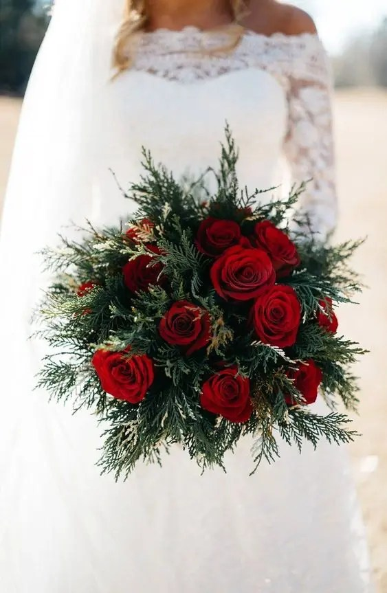a simple holiday wedding bouquet of evergreens and red roses is a chic idea