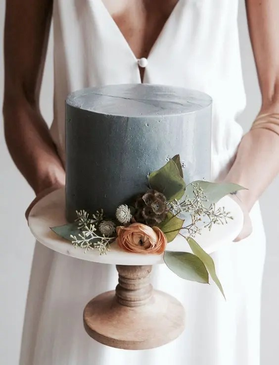a matte grey cake with fresh greenery and blooms is a cool idea for a modern winter wedding in grey