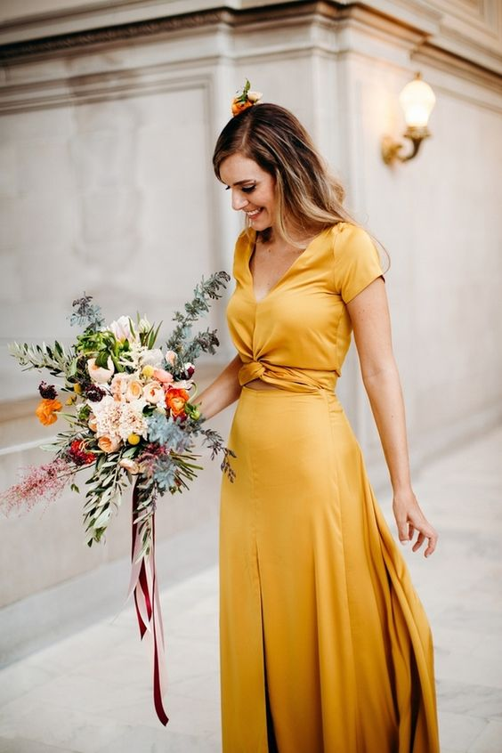 a beautiful gold yellow maxi dress with short sleeves, a V-neckline and a tied detail on the waist