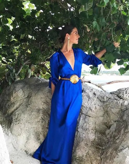 a fantastic bright blue maxi gown with a plunging neckline, long sleeves, statement earrings and a belt