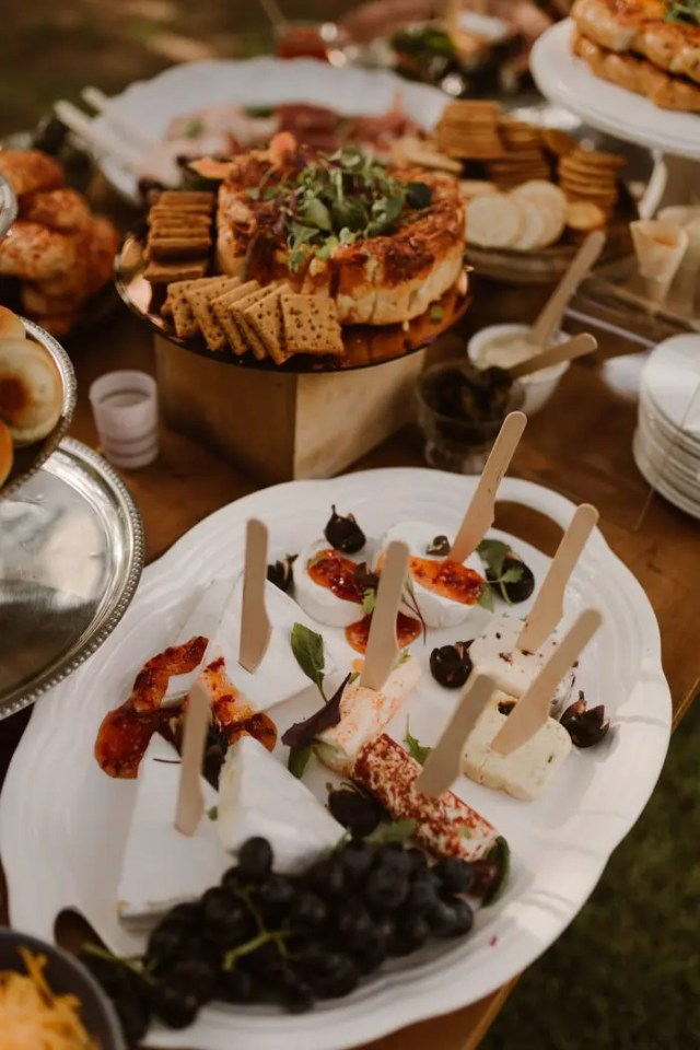 a chic charcuterie board with different types of cheese, grapes, crackers, meat and greenery
