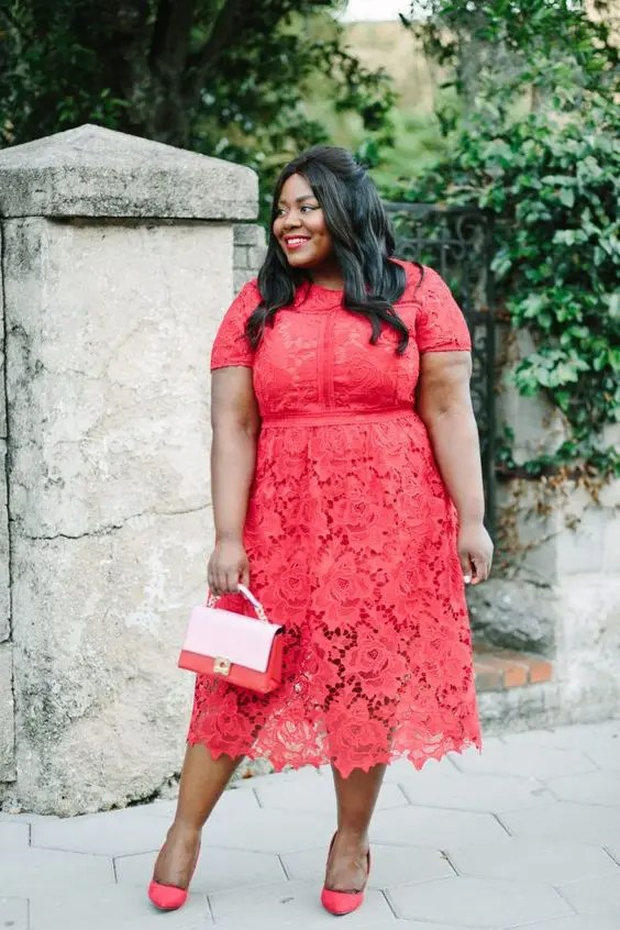 a coral lace midi dress with a high neckline, short sleeves and heels, a little bag