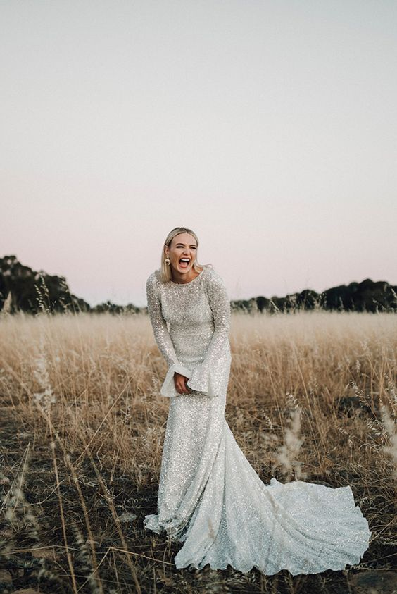 a sheath silver sequin wedding dress with bell sleeves and a train for a modern glam bride