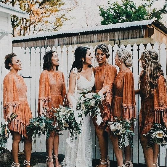 rust mini dresses with long fringed sleeves, high necklines and asymmetrical skirts for a boho wedding