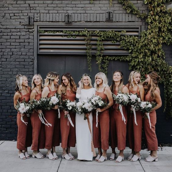 burnt orange midi fitting bridesmaid dresses with wide straps and mules for a boho wedding