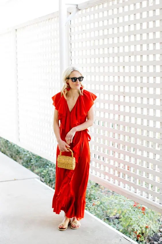 a red wrap ruffled maxi dress with cap sleeves, a small wicker bag and embellished sandals