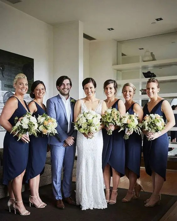 a bridesman wearing a light blue suit and girls rocking navy wrap gowns create a harmonious look