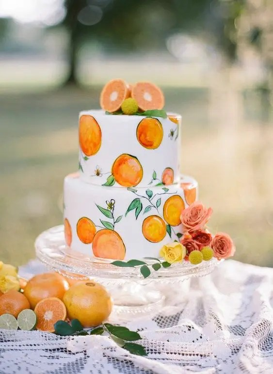 a cute handpainted wedding cake with painted and fresh fruits on top is a fun idea for a summer wedding