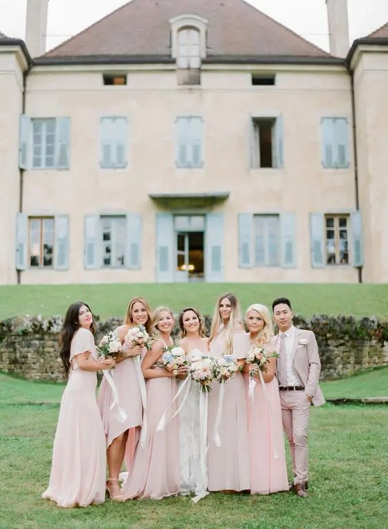 bridesmaids wearign pink dresses and a bridesman rocking a pink suit with a tie and a white shirt