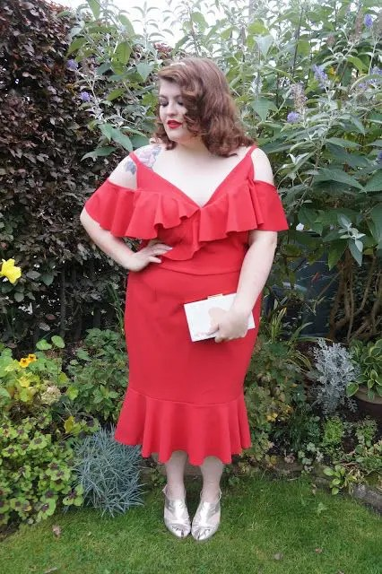 a red midi dress with a ruffled neckline, a cold shoulder, metallic shoes and a small white clutch