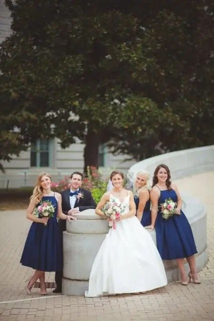 navy midi dresses with halter necklines match a grey suit with a navy bow tie to create an elegant party look