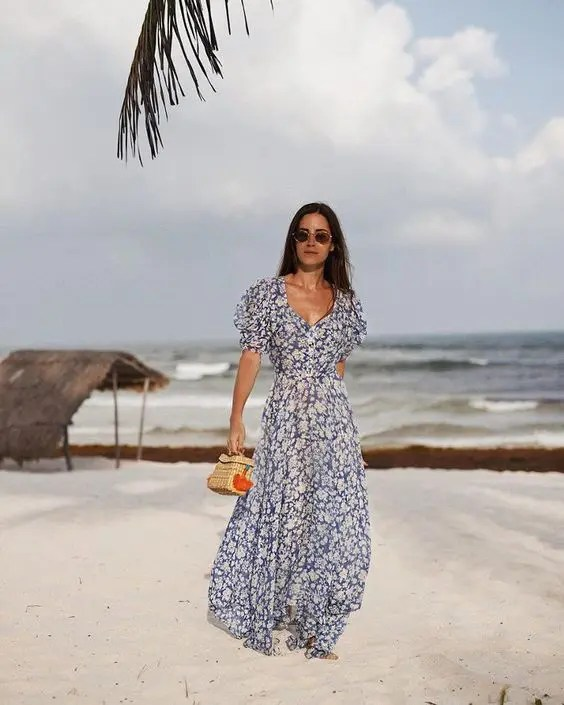 a gorgeous navy and white floral maxi gown with a deep neckline and short sleeves plus a small wicker bag