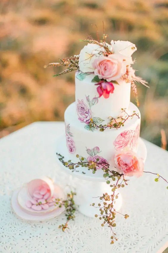 a chic handpainted wedding cake with blooms and greenery and flowers on top for a romantic wedding