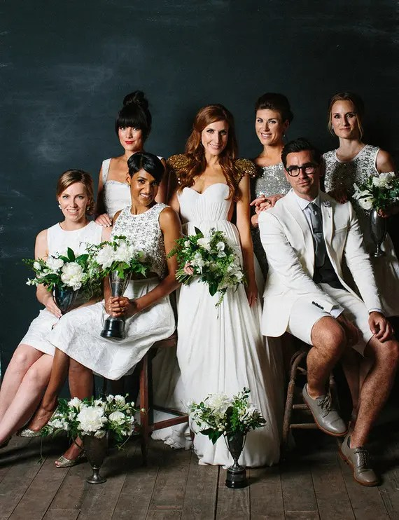 a white bridal party with a bridesman wearing a creamy suit with shorts, a grey tie and grey shoes