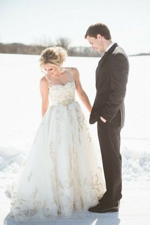 an illusion sweetheart neckline sleeveless wedding gown with gold embroidery and an embellished sash