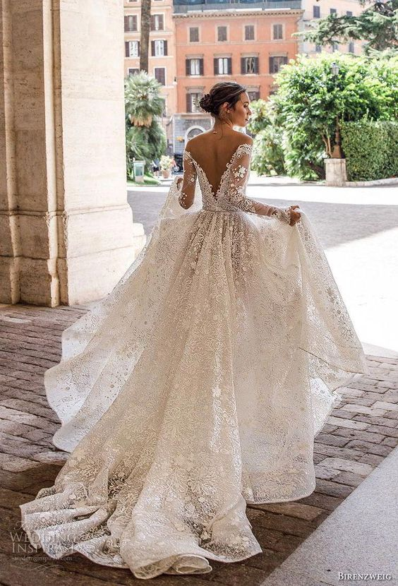 a floral lace ballgown with long sleeves, embellishments and a chapel train
