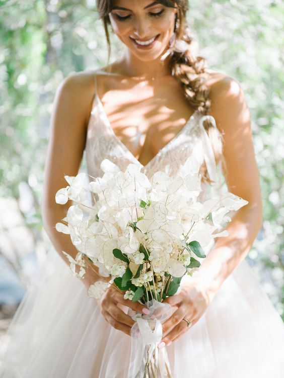 a chic and ethereal lunaria wedding bouquet with some berries and neutral ribbons looks beautiful