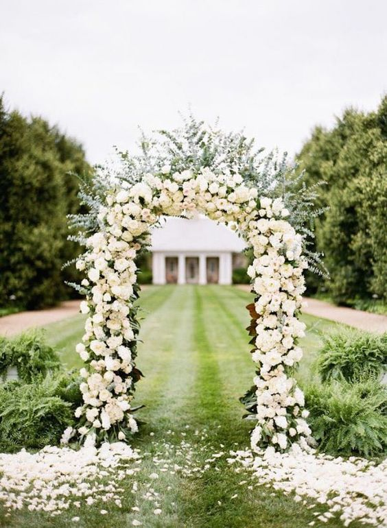 a curved wedding arch decorated with neutral roses and lush greenery plus lots of petals around