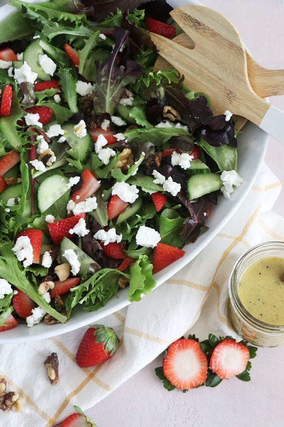 a fresh spring salad of goat cheese, strawberries, cucumbers and various kinds of greenery