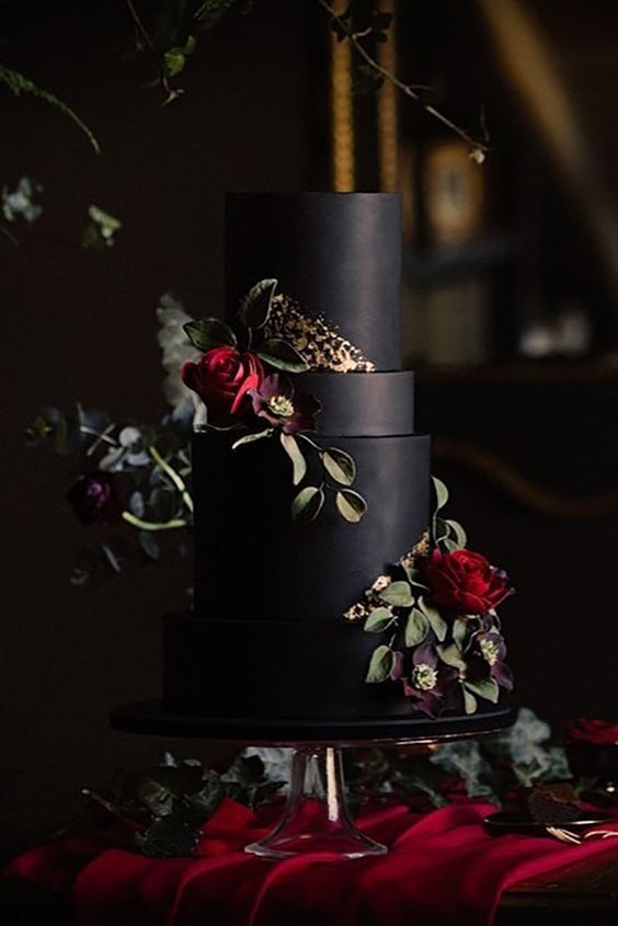 a matte black wedding cake with fresh and sugar blooms plus gold foil detailing