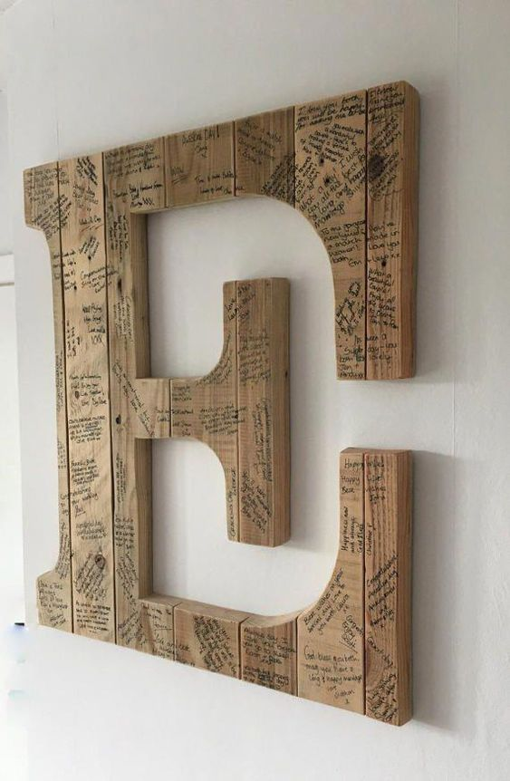 a wooden monogram signed by the guests can be used as an artwork, this is a cool and functional idea