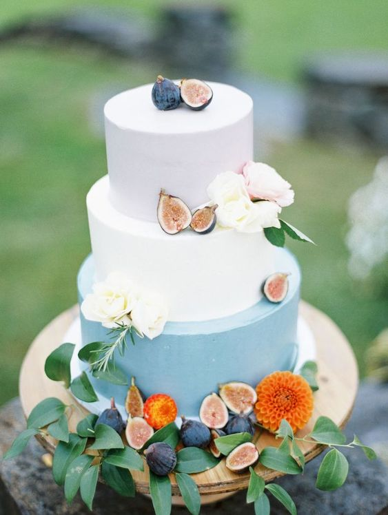 a blush, white and powder blue wedding cake topped with fresh blooms and figs
